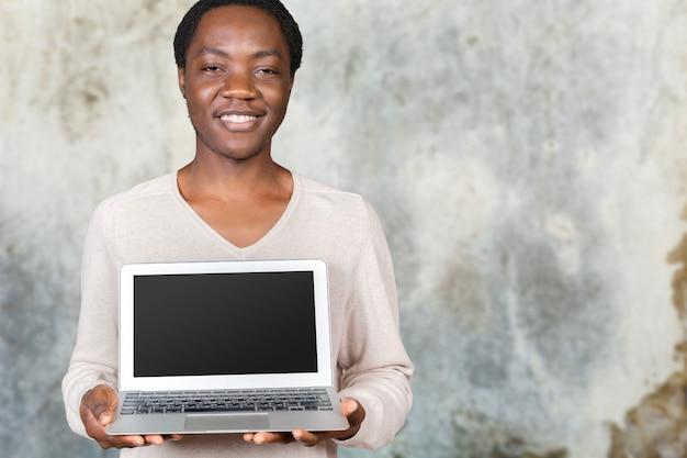 Szczęśliwy uśmiechnięty przystojny mężczyzna z laptopem