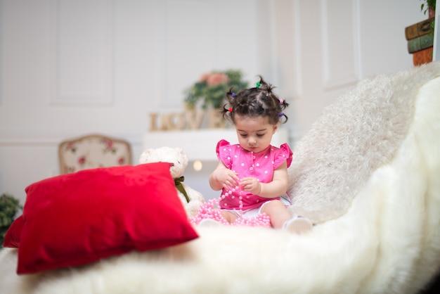 Szczęśliwy uśmiechnięty słodki dziewczynki obsiadanie na kanapie z niedźwiedź zabawką