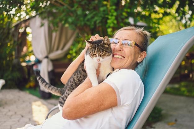 Szczęśliwy uśmiechnięty starszy starsza kobieta w okularach relaks w letnim ogrodzie na zewnątrz przytulanie domowego pręgowany kot. emerytowanych starych ludzi i zwierząt koncepcja zwierzęta