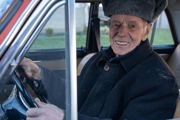Szczęśliwy uśmiechnięty stary człowiek jedzie retro samochód w czarnej kurtce, trzyma jej ręki na kole i patrzeje kamerę