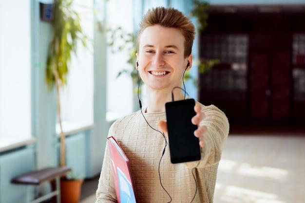 Szczęśliwy uśmiechnięty student w słuchawkach pokazujący ekran swojego telefonu do aparatu