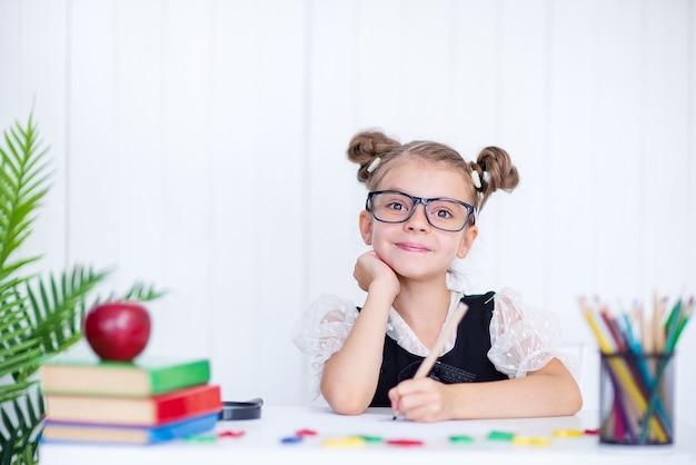 Szczęśliwy uśmiechnięty uczeń przy biurku. dziewczyna w klasie z ołówkami, książkami. dziewczynka ze szkoły podstawowej.