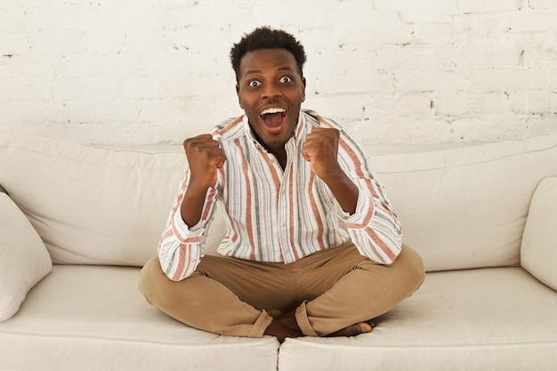 Szczęśliwy, uszczęśliwiony, młody afrykański kibic oglądający mecz w telewizji świętujący gola
