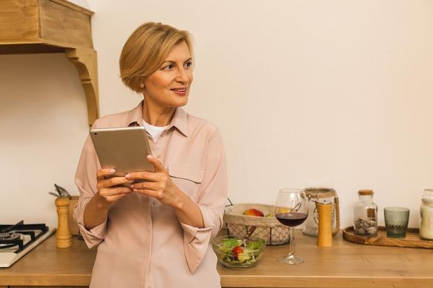 Szczęśliwy w średnim wieku 50 lat kobieta za pomocą cyfrowego tabletu, siedząc w kuchni w domu. starsza starsza pani trzymająca komputer z podkładką, znajdująca przepis, robiąca zakupy online, prowadząca wideorozmowę.