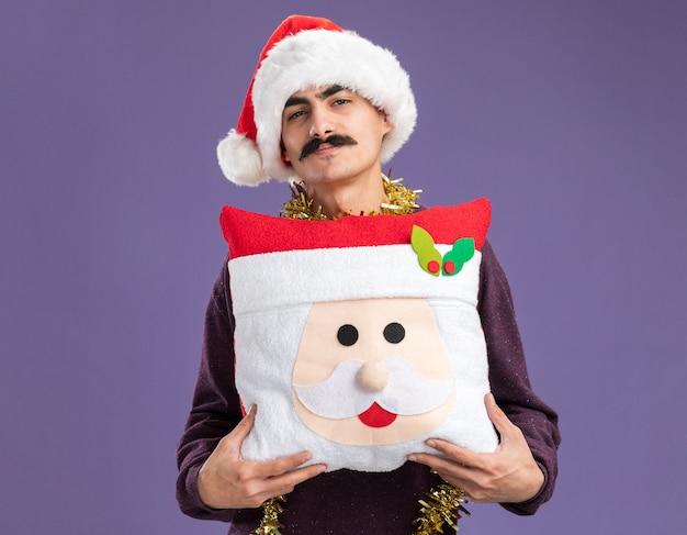 Szczęśliwy wąsaty mężczyzna w świątecznym kapeluszu mikołaja z blichtrem na szyi, trzymający świąteczną poduszkę z uśmiechem na twarzy, stojący nad fioletową ścianą