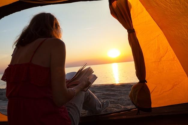 Szczęśliwy weekend nad morzem - dziewczyna czytała książkę w namiocie na plaży o świcie. ukraiński krajobraz nad morzem azowskim, ukraina