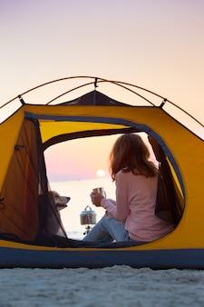 Szczęśliwy weekend nad morzem - dziewczyna w namiocie na plaży o świcie. ukraiński krajobraz nad morzem azowskim, ukraina