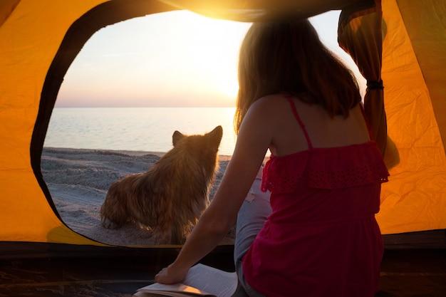Szczęśliwy weekend nad morzem - dziewczyna z psem w namiocie na plaży o świcie. ukraiński krajobraz nad morzem azowskim, ukraina