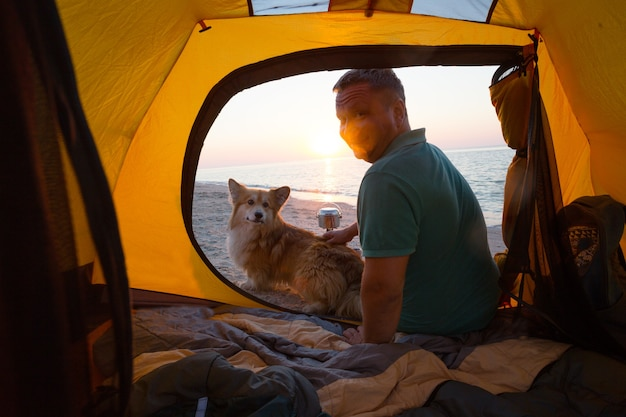 Szczęśliwy weekend nad morzem - mężczyzna z psem w namiocie na plaży o świcie. ukraiński krajobraz nad morzem azowskim, ukraina