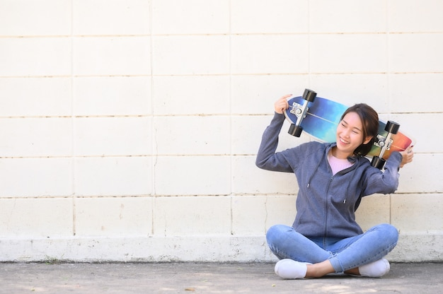 Szczęśliwy wesoły azjatki kobieta w stroju casual z surfskate siedząc przed betonową ścianą. koncepcja aktywnego stylu życia