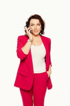 Szczęśliwy, wesoły bizneswoman rozmawia przez telefon komórkowy w różowym kolorze