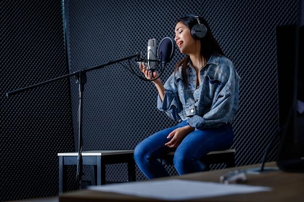 Szczęśliwy wesoły całkiem uśmiechający się portret młodej azjatyckiej kobiety spojrzeć na wokalistę smartfona w słuchawkach nagrywającego piosenkę z przodu mikrofonu w profesjonalnym studiu