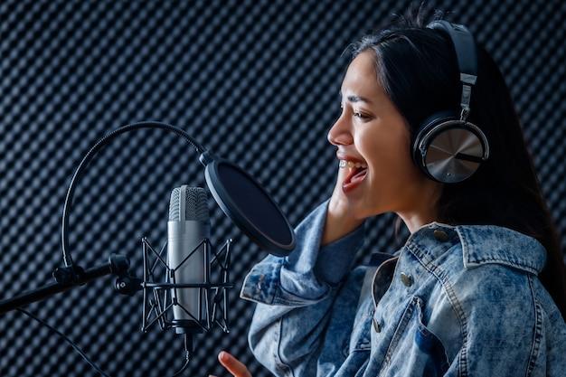 Szczęśliwy wesoły, całkiem uśmiechnięty portret młodej azjatyckiej wokalistki noszącej słuchawki nagrywającej piosenkę przed mikrofonem w profesjonalnym studiu