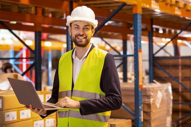 Szczęśliwy wesoły człowiek patrzy na ciebie podczas organizacji systemu logistycznego magazynu