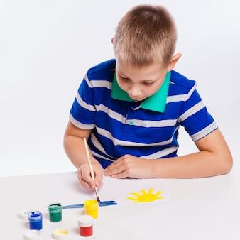 Szczęśliwy wesoły dziecko rysunek z pędzlem w albumie za pomocą wielu narzędzi do malowania. koncepcja kreatywności.