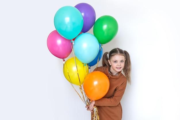 Szczęśliwy wesoły dziewczynka trzymając kolorowe kulki i uśmiechając się na białym backgraund. skopiuj miejsce na tekst