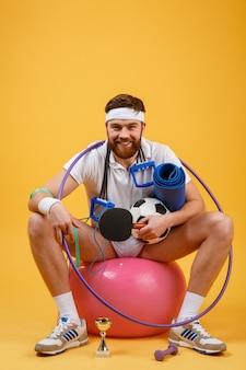 Szczęśliwy wesoły fitness mężczyzna siedzi na piłkę sportową