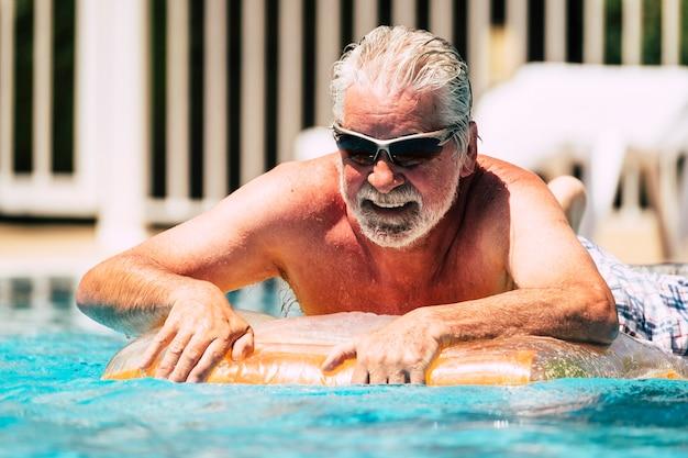 Szczęśliwy wesoły kaukaski starszy mężczyzna położył się na kolorowym modnym lilo, ciesząc się aktywnością rekreacyjną na świeżym powietrzu w basenie swimmin w okresie letnim na wakacje lub relaks w mieście