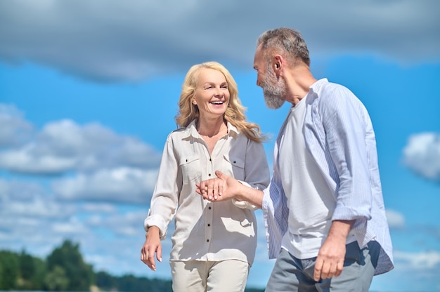 Szczęśliwy wesoły mężczyzna i kobieta spacerujący w naturze