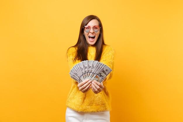 Szczęśliwy wesoły młoda kobieta w okularach serca krzyczy, trzymając pakiet wiele dolarów, pieniądze w gotówce na białym tle na jasnożółtym tle. ludzie szczere emocje, koncepcja stylu życia. powierzchnia reklamowa.