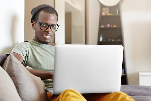 Szczęśliwy, wesoły młody ciemnoskóry mężczyzna, modnie wyglądający, siedzący w pomieszczeniu na szarej sofie z laptopem na kolanach, wysyłający wiadomości do znajomych lub oglądający seriale online, korzystając z szybkiego łącza internetowego w domu