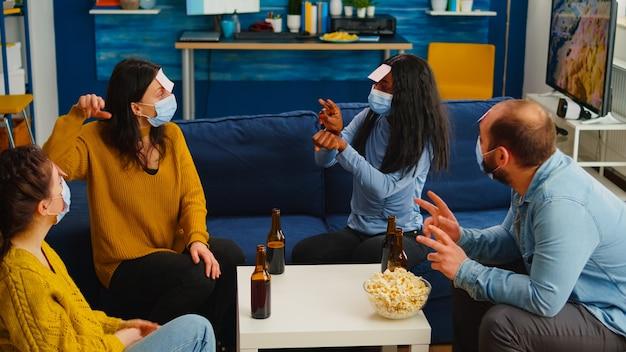 Szczęśliwy wesoły multi etniczni przyjaciele z maską na twarz grający w gry z karteczkami samoprzylepnymi na czole pijący piwo jedzący popcorn zgadujący zachowanie dystansu społecznego. podczas epidemii w domowym salonie