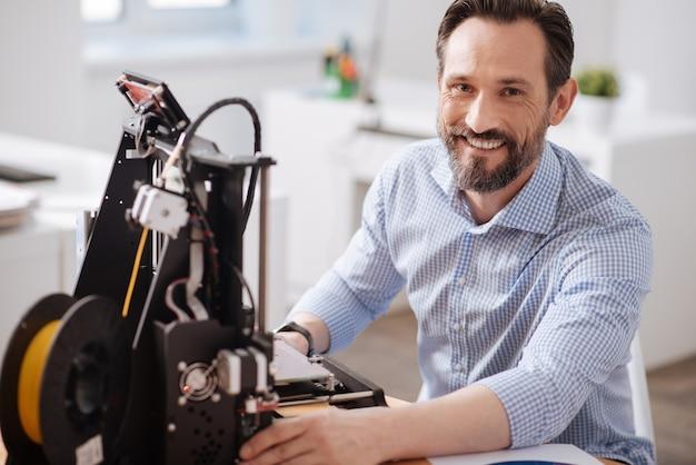 Szczęśliwy wesoły przystojny mężczyzna siedzi przy stole i uśmiecha się, ciesząc się pracą z technologiami 3d