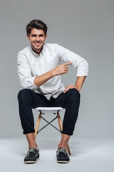 Szczęśliwy wesoły przystojny mężczyzna wskazując palcem dalej siedząc na krześle odizolowanym na szarej ścianie
