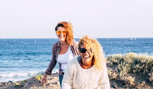 Szczęśliwy wesoły śmiejąc się piękna para kobiet na świeżym powietrzu, zabawy w przyjaźni, razem korzystających z wypoczynku na świeżym powietrzu z błękitnym oceanem i niebem na powierzchni