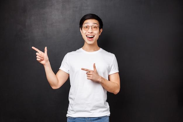 Szczęśliwy wesoły uśmiechnięty azjatycki mężczyzna jest podekscytowany, wskazując palcami w lewo i dopingując znalezioną doskonałą okazję ubiegania się o dobrą pracę, wymarzoną karierę lub firmę, która pomaga studiować za granicą, czarna ściana