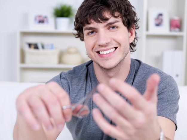 Szczęśliwy wesoły uśmiechnięty przystojny mężczyzna cięcia paznokci - w pomieszczeniu