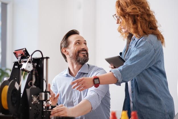 Szczęśliwy wesoły zachwycony koledzy patrząc na siebie i uśmiechając się, ciesząc się ze wspólnej pracy