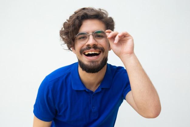 Szczęśliwy wesoły zadowolony facet dotykając okularów