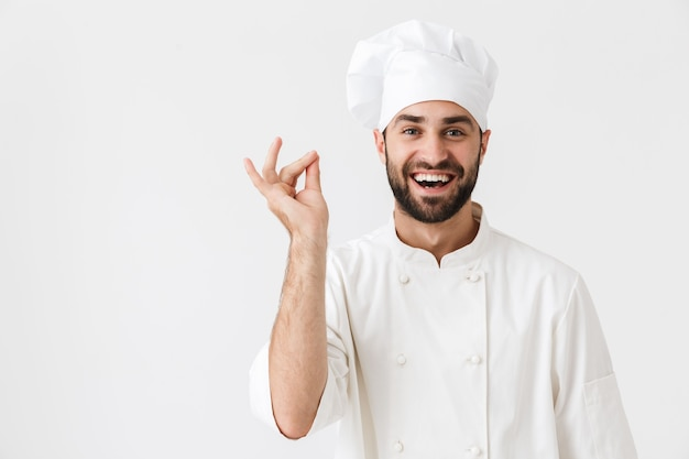 Szczęśliwy wesoły zadowolony młody kucharz pozowanie w mundurze gestykulacją.