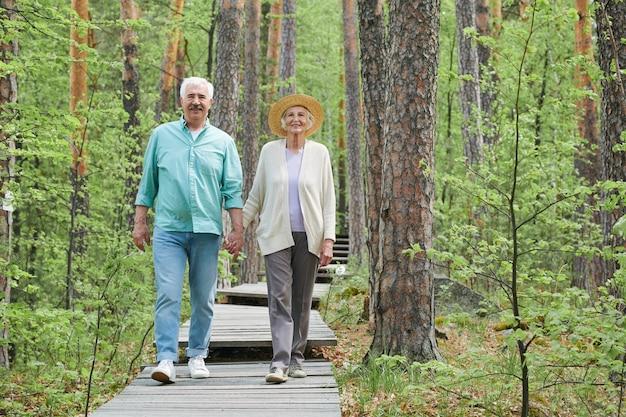 Szczęśliwy wieku emerytowany mężczyzna i kobieta trzymając się za ręce podczas przesuwania leśnej ścieżki wśród drzew w czasie wolnym