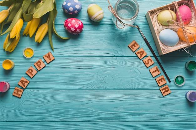 Szczęśliwy wielkanocny writing blisko jajek i farby
