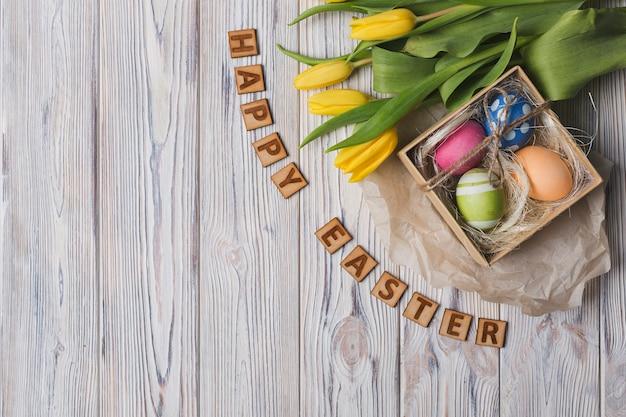 Szczęśliwy wielkanocny writing blisko tulipanów i jajek
