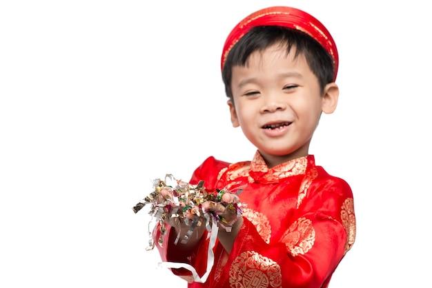 Szczęśliwy wietnamski chłopak w czerwonym ao dai świętuje nowy rok z konfetti. azjatyckie dziecko świętuje nowy rok