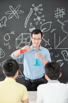 Szczęśliwy wietnamski nauczyciel chemii mieszający czerwone i niebieskie płyny na oczach uczniów, wyjaśniając podwójną reakcję zastępowania