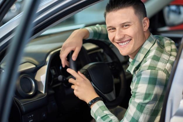 Szczęśliwy właściciel trzyma ręce na kierownicy pojazdu.