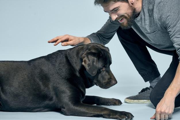 Szczęśliwy właściciel z czarnym psem, który go tresuje