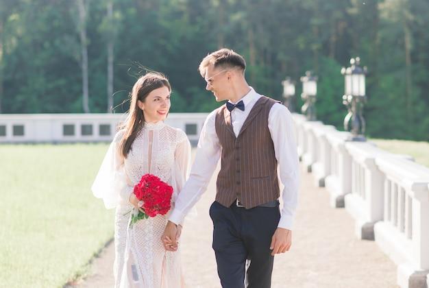Szczęśliwy właśnie żonaty młoda para świętuje i zabawy na świeżym powietrzu