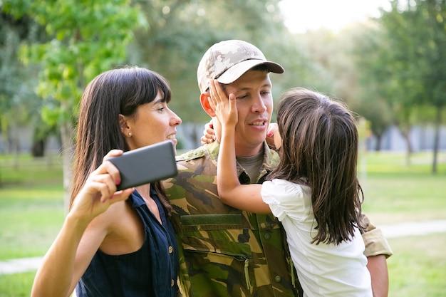 Szczęśliwy wojskowy, ciesząc się czasem z żoną i małą córeczką, biorąc selfie na telefon komórkowy w parku miejskim. sredni strzał. zjazd rodzinny lub koncepcja powrotu do domu