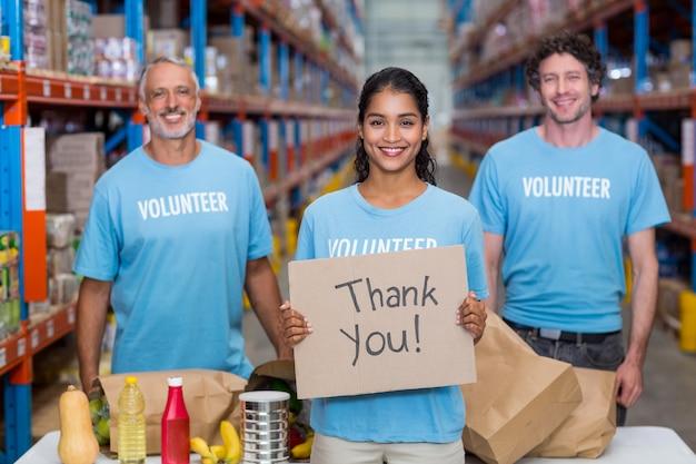 Szczęśliwy wolontariusz trzyma znak i pozuje z jej drużyną