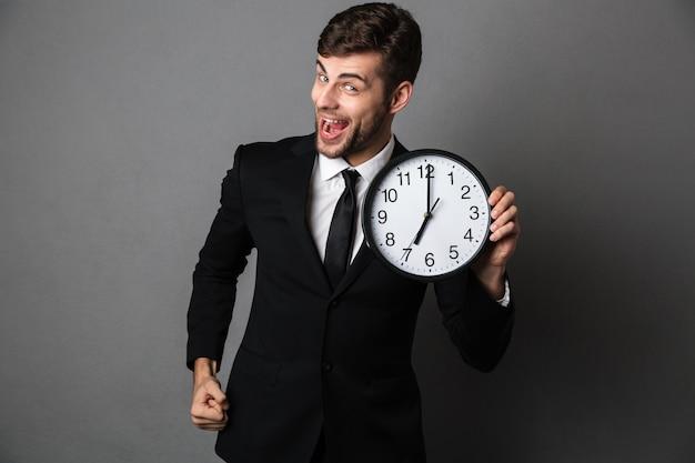 Szczęśliwy wychodzący brodaty mężczyzna w czarnym garniturze trzyma zegar,