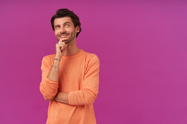Szczęśliwy wyglądający, marzący facet z brunetką i włosiem. ubrana w pomarańczowy sweter z podwiniętymi rękawami. dotykając jego brody