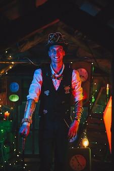 Szczęśliwy wynalazca mężczyzna w steampunkowym garniturze, cylindrze, okularach i uśmiechniętym laską w warsztacie zegarmistrzowskim