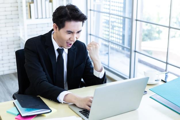 Szczęśliwy z azji młody biznesmen zobaczyć udany biznesplan na laptopie i piórze na tle drewniany stół