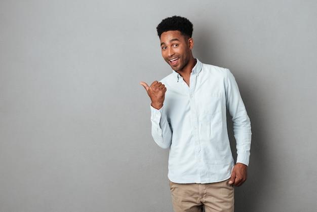 Szczęśliwy z podnieceniem afrykański mężczyzna wskazuje palec daleko od przy kopii przestrzenią