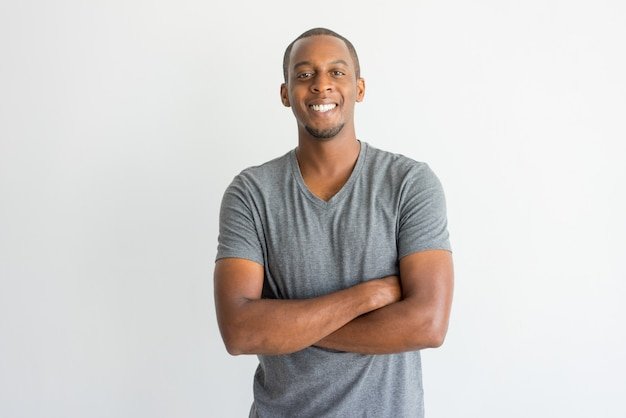 Szczęśliwy z podnieceniem młody afrykański mężczyzna ręk skrzyżowanie na klatce piersiowej i patrzeć kamerę.